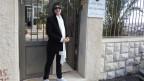Johanna Kawwas steht vor einem Tor. Sie trägt eine Sonnenbrille und einen weissen Schal.