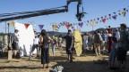Das Bild zeigt das Set von Papa Moll. Mit Kameras, Statisten und einem Zirkustzelt.