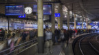 Pendler warten am Banhof Bern auf ihren Zug.