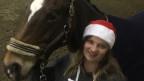 Svenja Berger steht neben ihrem Pferd «Chili» in der Reithalle.