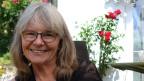 Auf dem Bild ist Susann Morand. Im Hintergrund hat es viele Rosen.