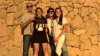 Nicole Bürgi steht mit ihrem Mann und ihren zwei Töchtern vor einer Steinwand.