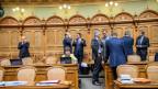 Männliche Politiker und eine Frau stehen und sitzen im Saal im Bundeshaus.