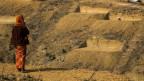 In einer sandigen, hügeligen Landschaft stehen einfache Hütten. Eine Frau in einem langen, rot-gemusterten Rock und dicker Jacke, ist unterwegs, dreht dem Fotografen den Rücken zu.