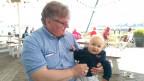 Urs Lüscher hält ein sein Enkelkind in Armen.