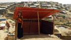Eine junge Frau in schwarzem, langem Jupe und farbigem Shirt steht vor einer einfachen Wellblechbehausung, die nach vorne offen ist.
