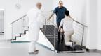 Patient der Rehaklinik Bellikon lernt auf einer Rampe wieder zu laufen.