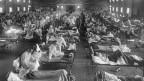 Ein Saal mit Spitalbetten und kranken Menschen