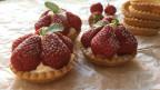 Drei Erdbeertörtchen mit diversen Törtchen-Bödeli im Hintergrund.