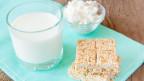 Ein Glas Milch, einen Nussriegel und Käse auf einem Tisch.