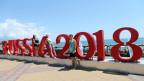 In Sotschi posieren Russinnen und Russen vor dem WM-Logo.