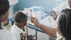 Eine Pflegerin verabreicht in Burkina Faso einem Kind Medizin mit einem Löffel, zwei weitere Personen in weissen Kitteln sehen dabei zu.