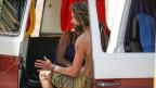Ein Hippie sitzt in einem offenen VW-Kombi
