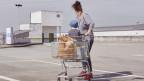 Eine Frau mit Kind und Einkaufswagen steht auf einem Parkplatz eines Einkaufszentrums