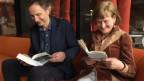 Res Strehle und Claudia Storz sitzen auf einem Sofa und lesen Lenz und Frisch