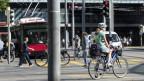 Velofahrerin im Stadtverkehr vor Bahnhof Bern.