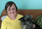 Frau mit Hund auf einem Sofa.