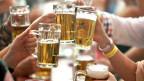 Leute prosten sich mit Bier zu.