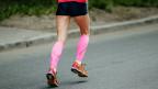 Läufer mit pinken Kompressionssocken.