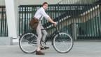 Mann steht mit dem Fahrrad vor einem Gebäude.