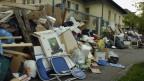 Viel Abfall liegt auf dem Trottoir einer Strasse.