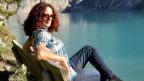 Helena Sommer-Murray sitzt auf einer Bank mit Aussicht auf einen See.