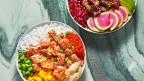 Bowls mit rohem Fisch, Reis, verschiedenen Gemüsen und Früchten