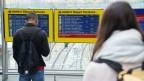 Menschen stehen vor SBB Anzeigetafel. Darauf steht Zugsausfall.