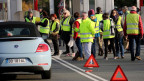 Menschen in gelben Westen stehen auf der Strasse.