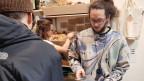 Mann verkauft Bio-Produkte über einen Holztresen