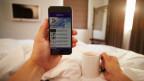 Ein Mann liegt im Bett und liest die News auf dem Smartphone.