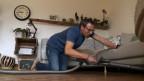 Markus Blum am Staubsaugen kniet auf dem Boden