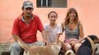 Andrea Martin sitzt mit ihrem Mann und ihrer Tochter auf einer Bank. Vor ihr stehen ihre drei Hunde.