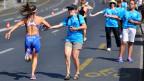 Freiwillige Helfer verteilen Wasser an Triathleten.