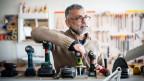 Finalist Johny Padua stützt sich in seinem Tüftellabor auf einen Tisch voller Akkubohrer. Im Hintergrund hängen Werkzeuge an der Wand.
