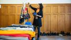 «Helden des Alltags»-Finalistin Jennifer Perez betrachtet an einer Kleiderbörse einige Handtaschen.