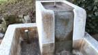 Ein verschmutzter Brunnen aus Granit.