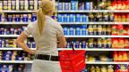 Frau steht vor Supermarktregal.