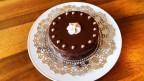 Kleine Wiener Sachertorte, schön dekoriert auf einem Teller mit weissen Spitzen.