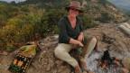 Nora Leuenberger sitzt auf einem Berg und trägt einen Cowboyhut.