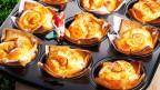 Kleine gebackene Käseküchlein in einer Muffinform.