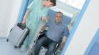 Mann verlässt Spital im Rollstuhl.