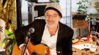 Roli Frei mit Kappe, Gitarre und Mikrophon
