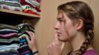 Ein Mädchen steht vor ihrem Kleiderschrank.