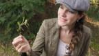 Doris Abt mit Hut und Brennnessel in der Hand.