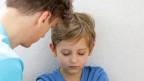 Ein Vater redet ruhig auf sein Kind ein, dass mit angezogenen Beinen und geschlossenen Augen am Boden sitzt.