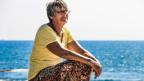 Eine ältere Frau sitzt am Meer.
