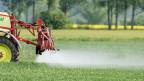 Ein Bauer besprüht sein Feld