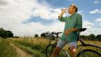 Mann trinkt während Fahrradtour