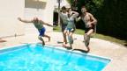 Menschen springen in den Pool.